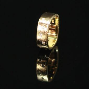 Ring lavet af gammelt guld, vielsesringe og frierring. Hun ville gerne have noget større, hvor alle hendes sten samtidig kom til sin ret.