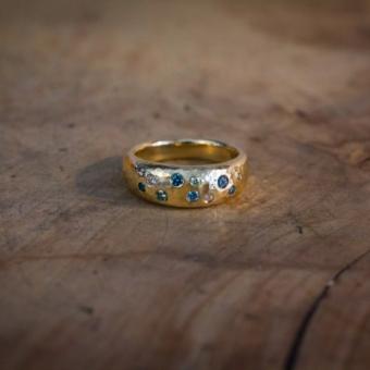 Bånd ring i gammelt guld med blå, grønne og hvide brillanter.